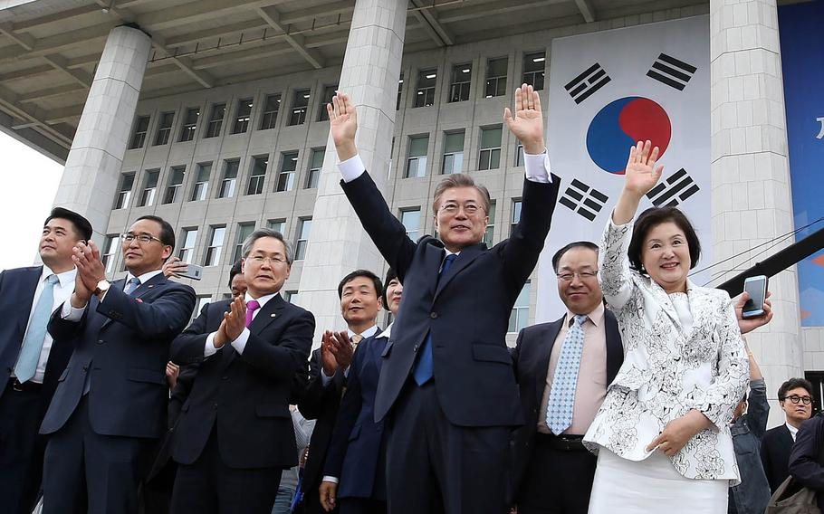 New South Korean President Moon Jae-in and his wife, Kim Jung-suk, wave to supporters in Seoul, Wednesday, May 10, 2017.