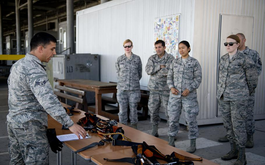 Airman 1st Class Hector Montoya describes to fellow 721st Aerial Port Squadron members how to properly inspect and wear harnesses during annual fall protection training at Ramstein Air Base, Germany, on Wednesday, May 10, 2017.