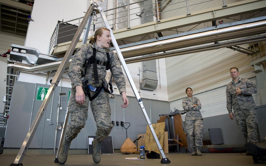 Senior Airman Sarah Isbell hangs in a harness during the 721st Aerial Port Squadron's annual fall protection training at Ramstein Air Base, Germany, on Wednesday, May 10, 2017. APS personnel took turns hanging in the harness to feel the effects of a fall.