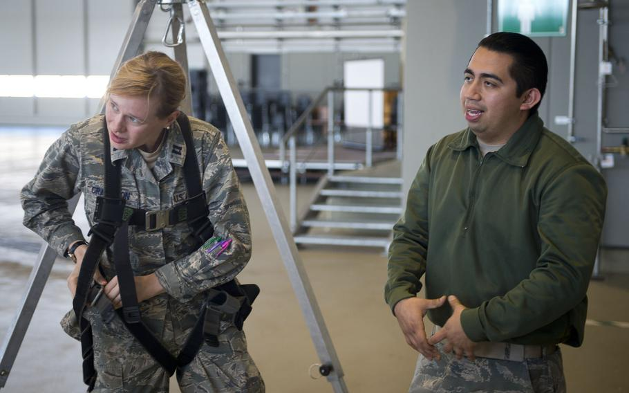 Staff Sgt. Ulysses Arango, right, describes the different types of harnesses as Capt. Teresa Crampton tightens her straps during fall protection training at Ramstein Air Base, Germany, on Wednesday, May 10, 2017. Arango is from the 721st Aircraft Maintenance Squadron and Crampton is from the 721st Aerial Port Squadron.