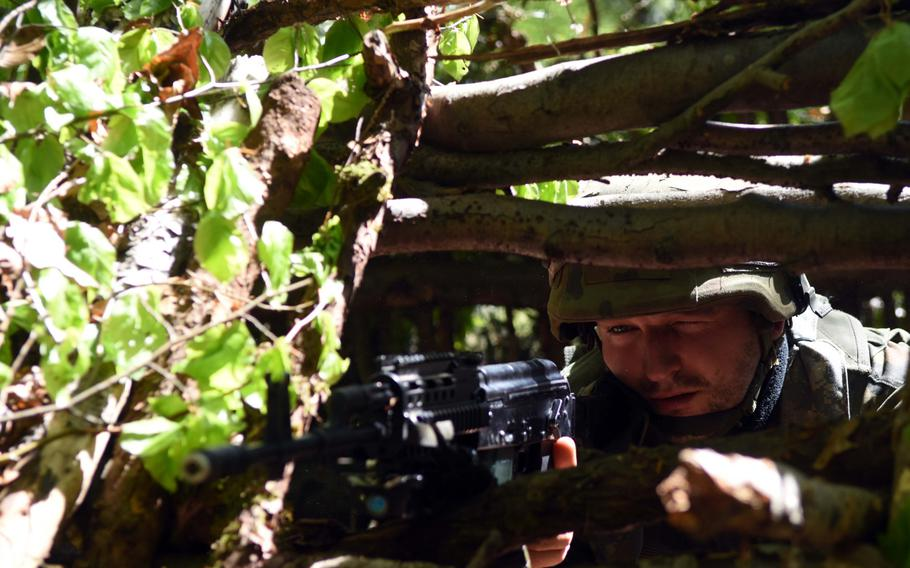 A Polish soldier with American and British forces in Hohenfels, Germany, takes aim and surveys his surroundings during Exercise Saber Junction, Wednesday, May 10, 2017.
