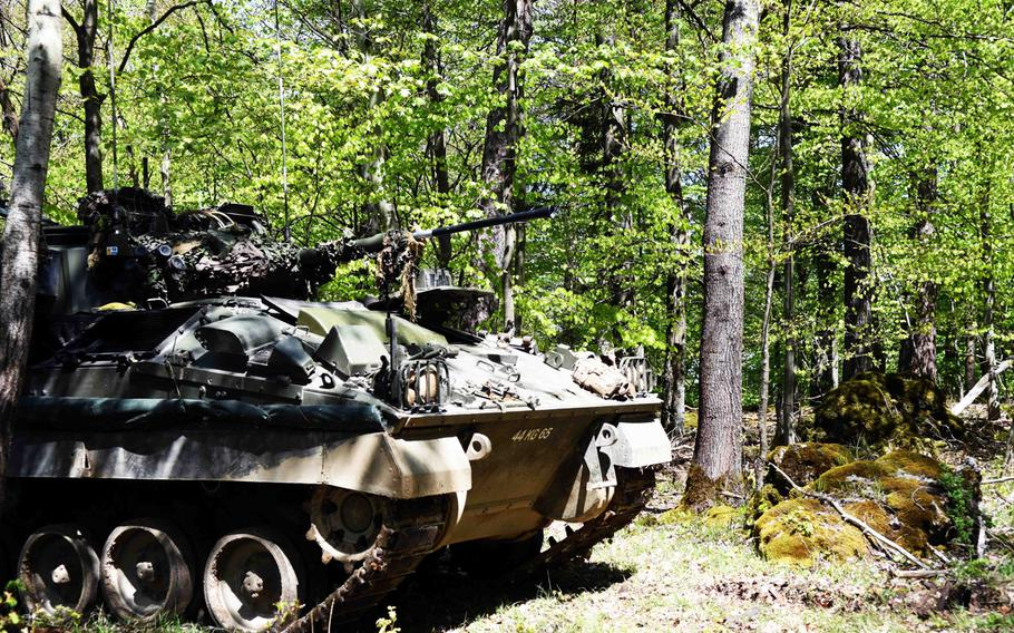A British Warrior Observation Post Vehicle waits in the woods in Hohenfels, Germany, concealed from simulated enemy forces during Exercise Saber Junction, Wednesday, May 10, 2017.