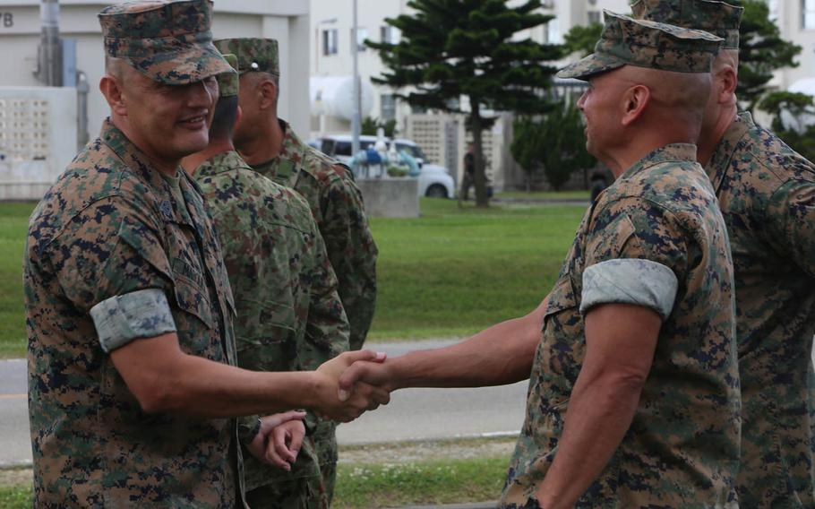 Sgt. Maj. Mario Marquez, left, greets III Marine Expeditionary Force Marines during a ceremony at Camp Hansen, Okinawa, Friday, May 12, 2017. Marquez replaced Sgt. Maj. Lee Bonar Jr. as the III Marine Expeditionary Force sergeant major.