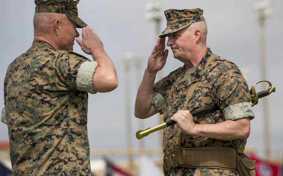Sgt. Maj. Lee Bonar Jr., right, hands off the sword of the III Marine Expeditionary Force command sergeant major to III MEF's commander, Lt. Gen. Lawrence Nicholson, at Camp Hansen, Okinawa, Friday, May 12, 2017.