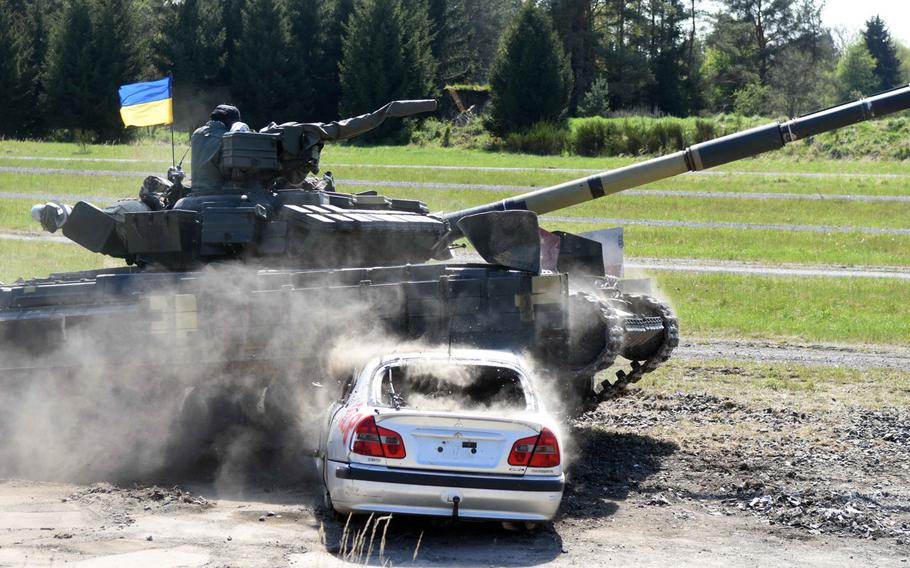 Ukrainian tankers drive a T-64BM tank through a car set up as an obstacle during a portion of the Strong Europe Tank Challenge at Grafenwoehr, Germany, Thursday, May 11, 2017.