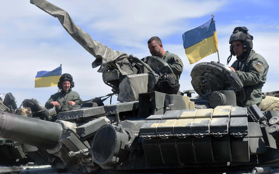 Ukrainian tankers atop a T-64BM tank get ready to maneuver their tank through obstacles during the Strong Europe Tank Challenge at Grafenwoehr, Germany, Thursday, May 11, 2017.