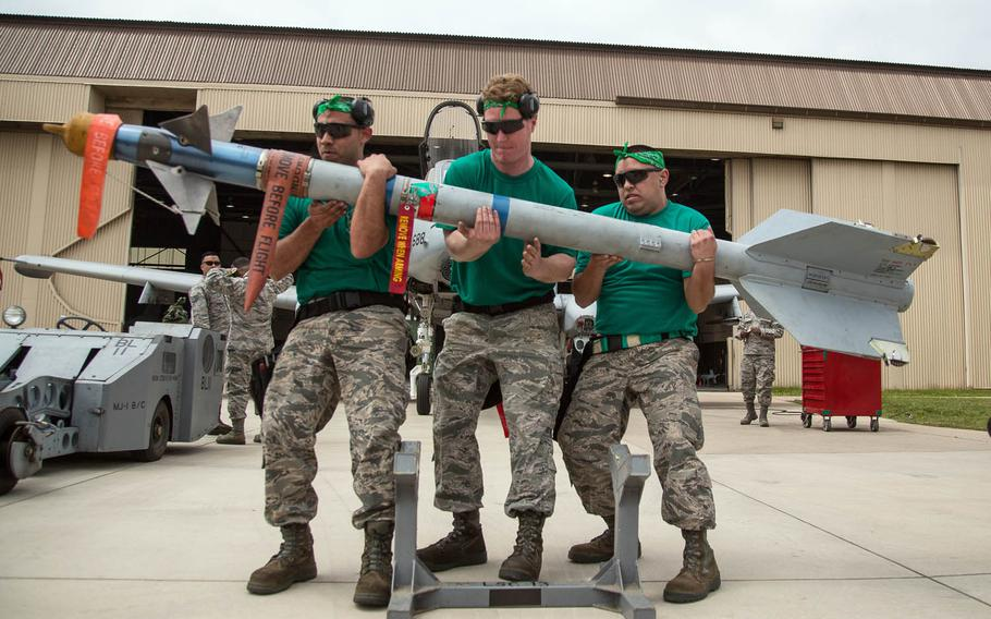 Competitors lift a weapon during the 2017 Annual Load Crew Competition at Kunsan Air Base, South Korea, Saturday, May 13, 2017.