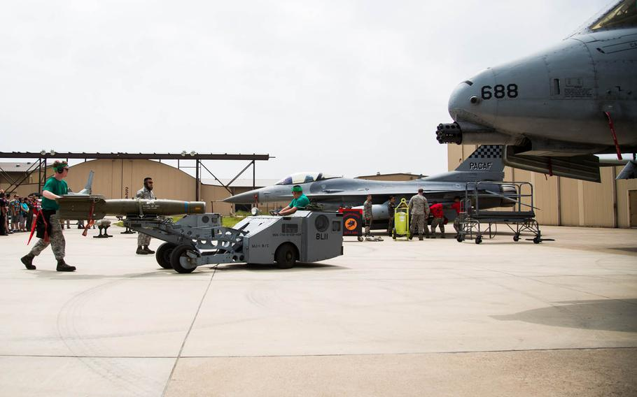 Competitors load a bomb onto a jet with a jammer during the 2017 Annual Load Crew Competition at Kunsan Air Base, South Korea, Saturday, May 13, 2017.
