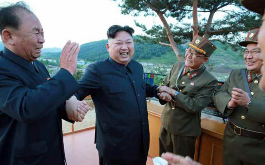 North Korean leader Kim Jong Un smiles as he apparently celebrates the test launch of a new type of missile, Sunday, May 14, 2017.
