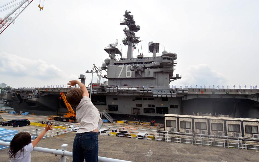 Aryanna Abriam, 10, right, and Ailani Abriam, 4, left, wave goodbye to their father as the aircraft carrier USS Ronald Reagan prepares to depart Yokosuka Naval Base, Japan, Tuesday, May 16, 2017.