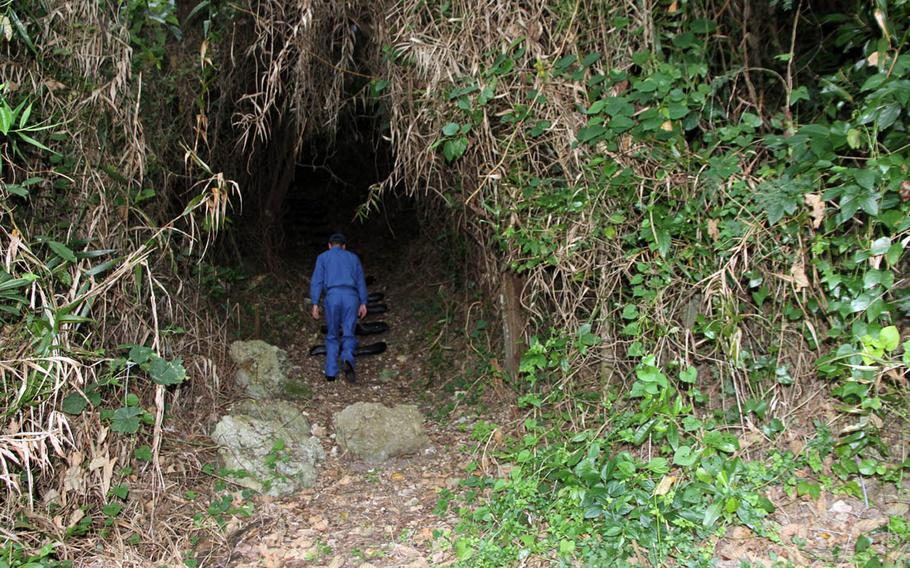 A Japan Maritime Self-Defense Force sailor begins the long journey up to one of the Heshikiya community's most sacred sites at a U.S. military installation on Okinawa.