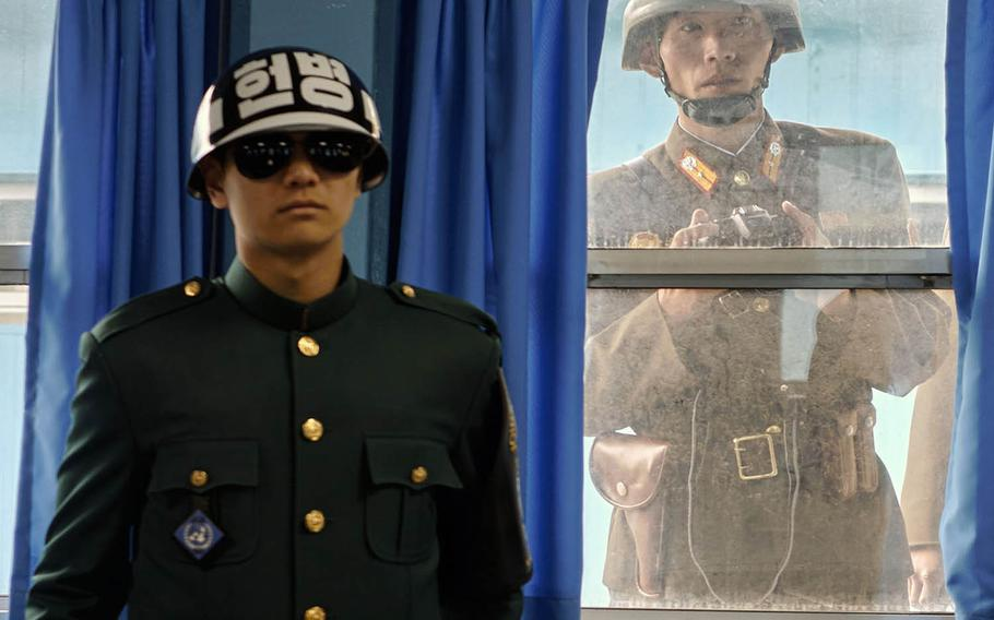 A North Korean soldier looks over the shoulder of a South Korean soldier inside the United Nations Command Military Armistice Commission Conference Building at the Joint Security Area of the Demilitarized Zone between North and South Korea, in November 2015.