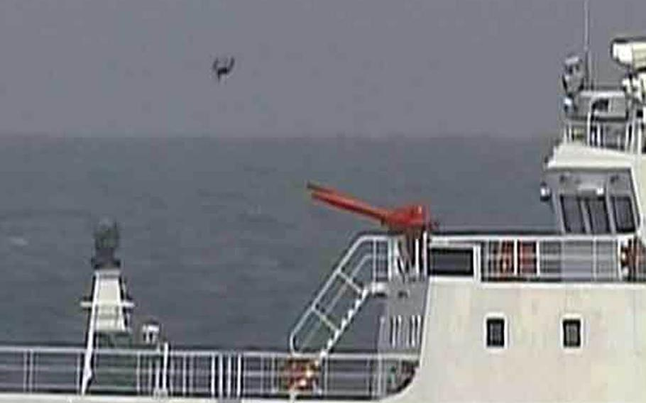 What appears to be a drone aircraft flies near Chinese coast guard vessels that entered Japanese waters near the Senkaku Islands, Thursday, May 18, 2017.