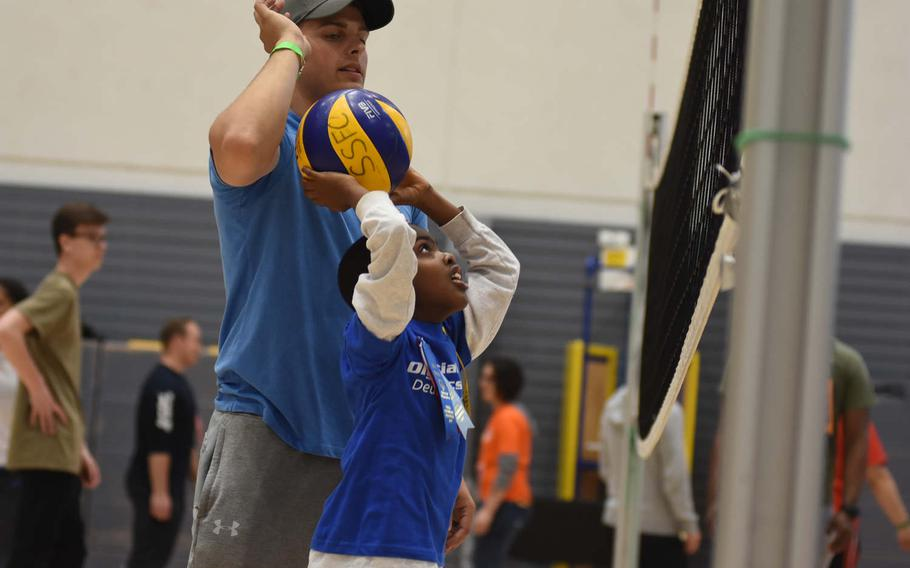 Senior Airman Allen Silker helps Sam Hussey,7, of Ramstein Elementary School toss the ball over the net while playing volleyball on Friday, May 19, 2017, during the KMC Rheinland-Pfalz Special Olympics at Ramstein Air Base, Germany. About 75 athletes and 300 volunteers participated.