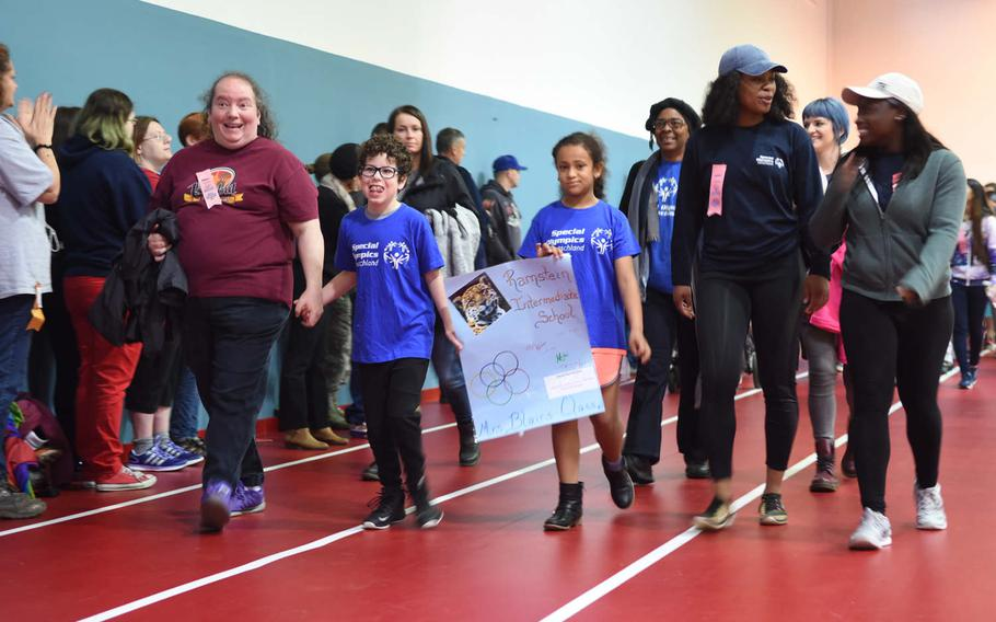 """Student athletes participating in the KMC Rheinland-Pfalz Special Olympics walk with their """"buddies"""" during the games' opening march on Friday, May 19, 2017. Due to the rain, most activities were held indoors at the Southside Fitnes Center on Ramstein Air Base, Germany."""