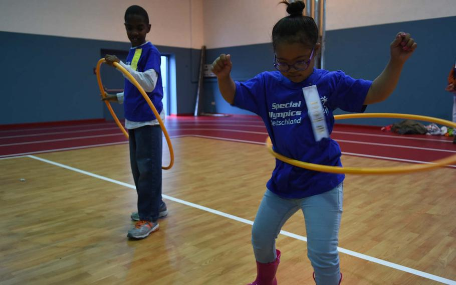 Aviella Simpkins, 7, a student at Vogelweh Elementary School in Kaiserslautern, Germany, shows her skills with the hula hoop while Sam Hussey, 7, of Ramstein Elementary School looks on. The two were participating in the KMC Rheinland-Pfalz Special Olympics at Ramstein Air Base, Germany, on May 19, 2017.