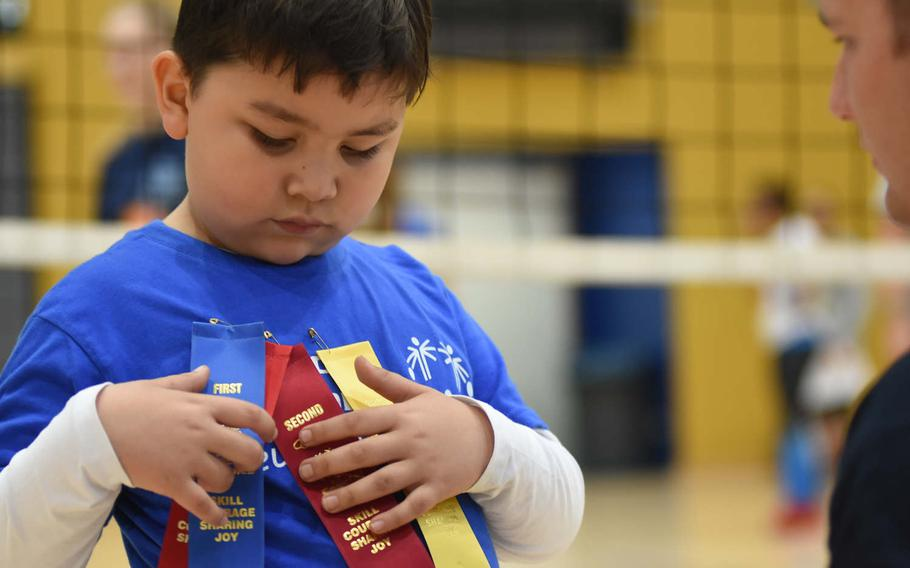 """Markus Bayquen, 6, of Vogelweh Elementary School, Germany, looks at the array of ribbons pinned on his shirt during the KMC Rheinland-Pfalz Special Olympics on Friday, May 19, 2017, while his """"buddy,"""" Airman 1st Class Bradley Dickey looks on. The games were held at Ramstein Air Base, Germany."""