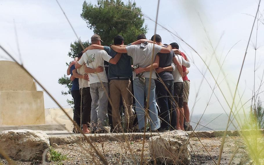 A former Israeli special operations team tgathers as a group for a private moment along Israel's Mediterranean coastline during their participation in the Peace of Mind program which treats full special operations units for post-combat trauma.