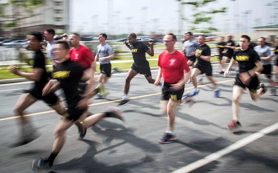 Soldiers race a 5K while carrying .50-caliber machine gun barrels during the 1st Armored Brigade Combat Team, 1st Infantry Division's centennial celebration at Camp Humphreys, South Korea, Wednesday, May 24, 2017.