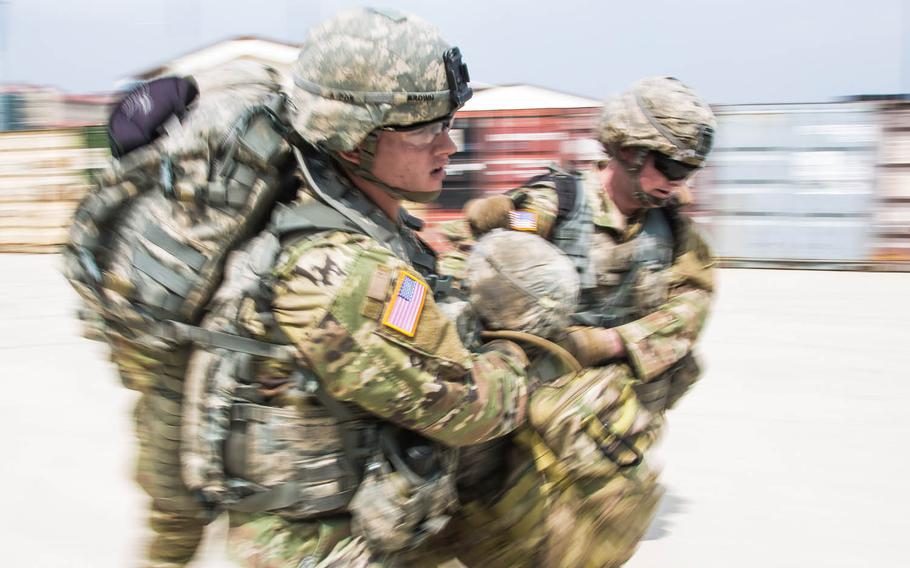 """Soldiers carry a simulated casualty as part of a """"Warrior Competition"""" during the 1st Armored Brigade Combat Team, 1st Infantry Division's centennial celebration at Camp Humphreys, South Korea, Wednesday, May 24, 2017."""