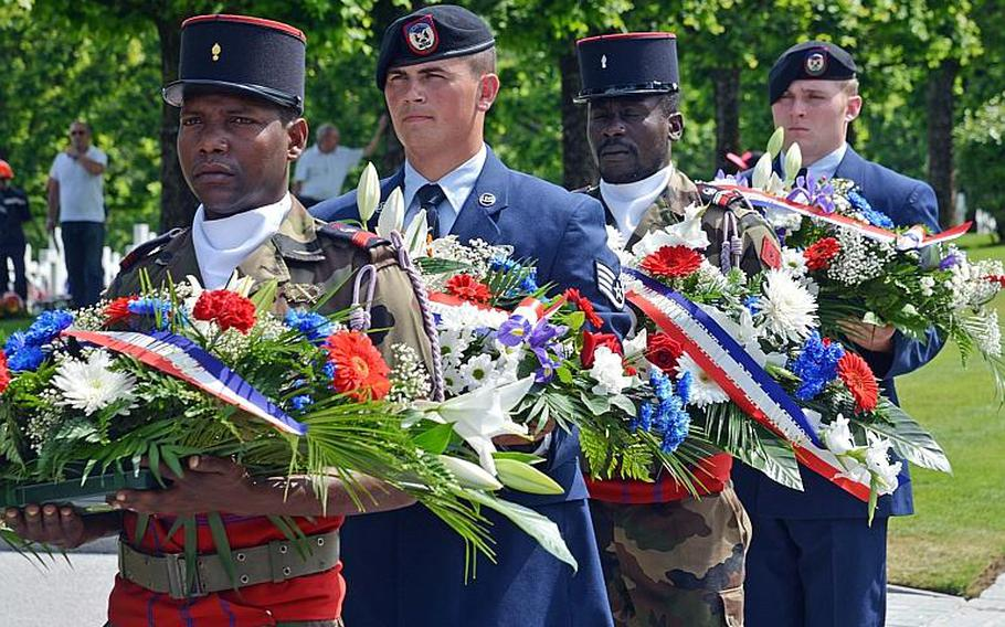 French and American servicemembers, including Staff Sgt. William Cole and Senior Airman Jordan Renfrow, hold floral arrangements during the Memorial Day ceremony at Meuse-Argonne American Cemetery in Romagne-sous-Montfaucon, France, Sunday May 28, 2017. The airmen are with Detachment 1, 4th Air Special Operations Group in Hohenfels, Germany.