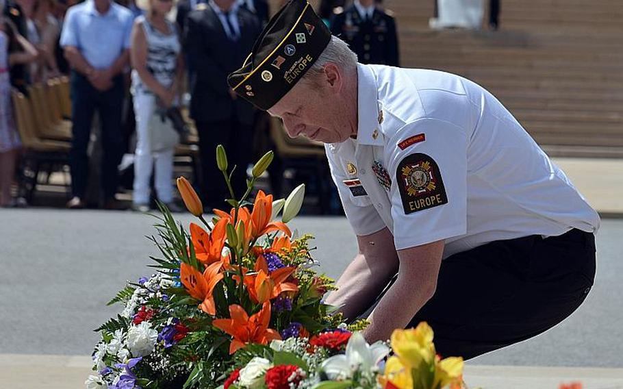 Alan Henrichson of Veteran's of Foreign Wars Post 27 presents a floral arrangement at the Memorial Day ceremony at Meuse-Argonne American Cemetery in Romagne-sous-Montfaucon, France, Sunday May 28, 2017.