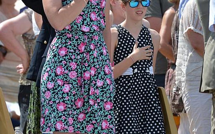 Kelly Lee and her daughter, Lauren, from Ramstein, Germany, hold their hands over their hearts during the playing of the national anthem the Memorial Day ceremony at Meuse-Argonne American Cemetery in Romagne-sous-Montfaucon, France, Sunday May 28, 2017.