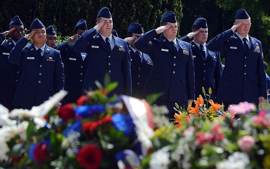 American volunteers from Ramstein Air Base salute during the playing of the French equivalent of ''Taps'' at the Memorial Day ceremony at Meuse-Argonne American Cemetery in Romagne-sous-Montfaucon, France, Sunday May 28, 2017.