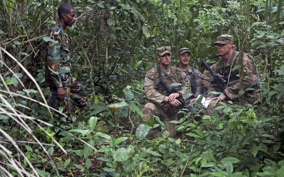 Ghana Armed Forces Sgt. Kofi Francis Donkor observes as U.S. soldiers assigned to the 1st Battalion, 506th Infantry Regiment, 1st Brigade Combat Team, 101st Airborne Division,  navigate through the jungle during United Accord 2017 at the Jungle Warfare School at Achiase military base, Akim Oda, Ghana, May 26, 2017.