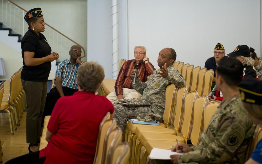 Verna Jones, American Legion Executive Director, left, listens to comments by U.S. Army Master Sgt. Tyler Brown during a town hall meeting in Kaiserslautern, Germany, on Wednesday, May 31, 2017.