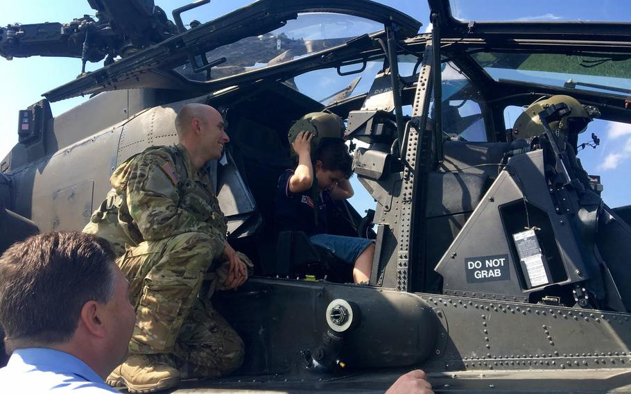 A U.S. Army AH-64 Apache helicopter from Katterbach landed in a farmer's field Wednesday, May 31, 2017, after a sensor went off while on a routine training mission in southern Germany. Capt. Ben Dagg let children sit in the cockpit and try on his flight helmet while the Apache waited to return to flight.