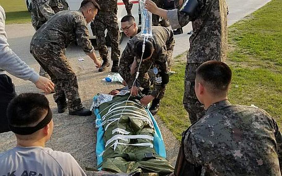 U.S. and South Korean soldiers attached to the United Nations Command Security Battalion in the Joint Security Area on the border with North Korea rush a South Korean farmer to a U.S. Forces Korea helicopter that carried him to a hospital on May 31, 2017.