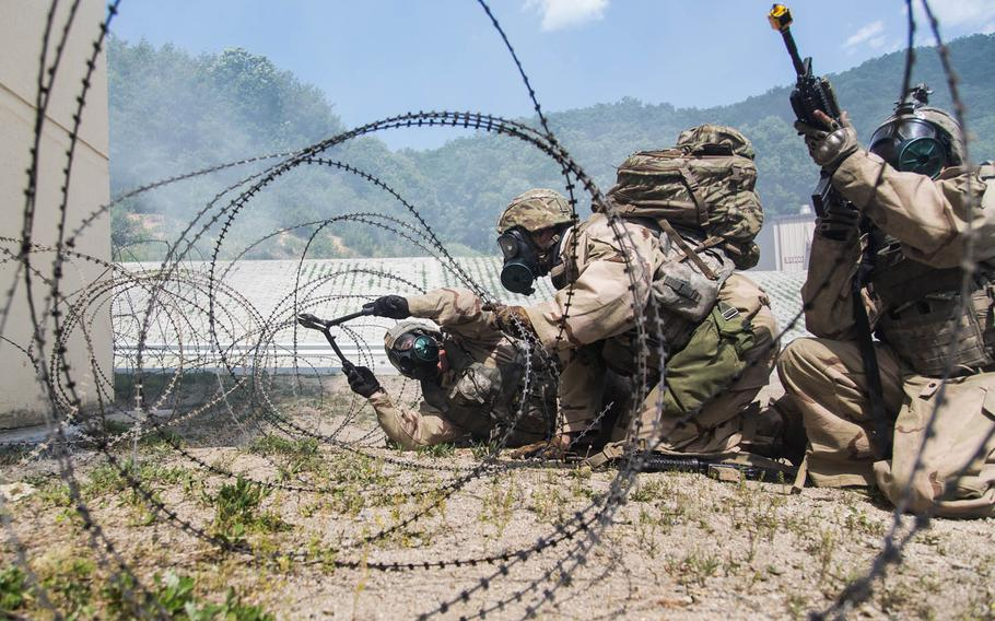 Soldiers from 1st Battalion, 5th Infantry Regiment, 1st Stryker Brigade Combat Team, 25th Infantry Division out of Fort Wainwright, Alaska, cut through concertina wire as they clear buildings at Rodriguez Live Fire Range, South Korea, Sunday, June, 4, 2017.