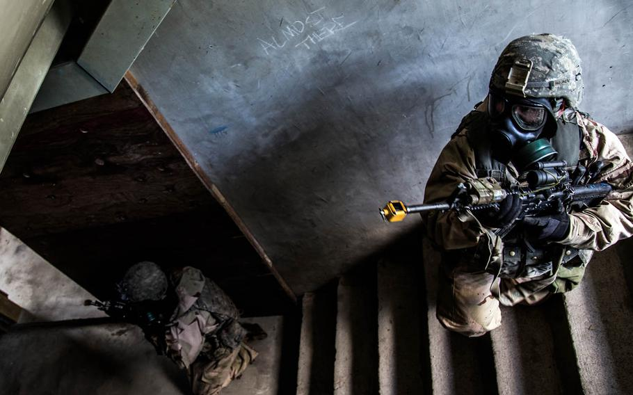Soldiers from 1st Battalion, 5th Infantry Regiment, 1st Stryker Brigade Combat Team, 25th Infantry Division out of Fort Wainwright, Alaska, keep watch over a stairwell during a drill at Rodriguez Live Fire Range, South Korea, Sunday, June, 4, 2017.