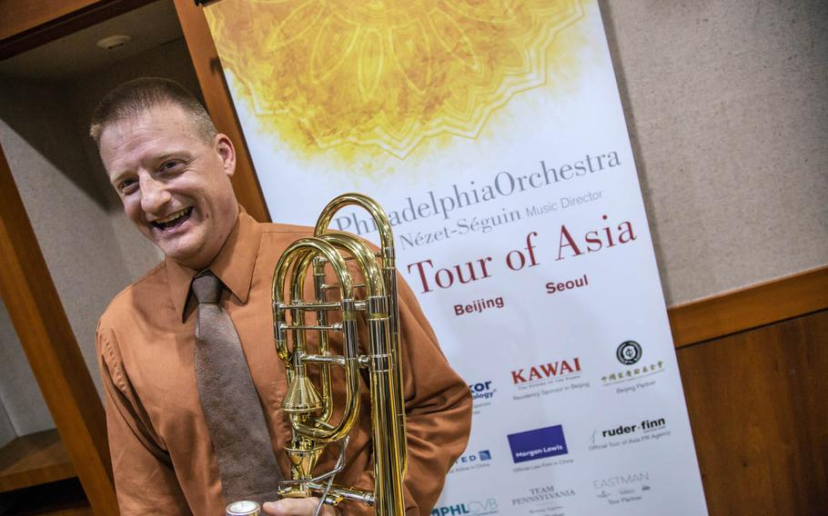 Staff Sgt. James Beeson, a trombonist for the 8th Army Band, holds the trombone of his idol, world-renowned bass trombonist Blair Bollinger, backstage at the Seoul Arts Center's Music Hall, Thursday, June 8, 2017.