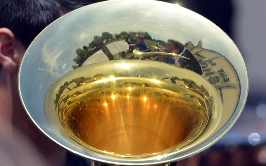 The Bitburg High School band and the school are reflected in a horn at the school's closing ceremony in Bitburg, Germany, Thursday, June 8, 2017.