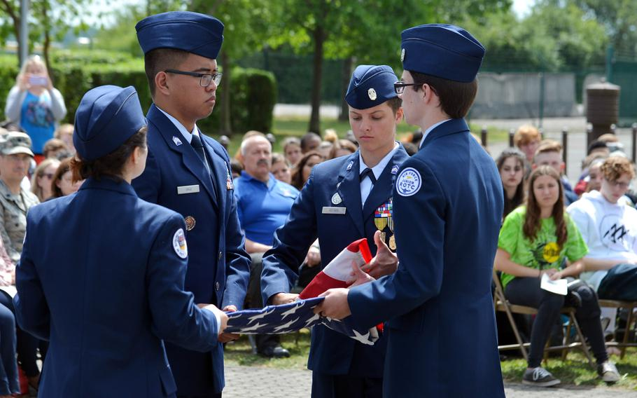After lowering the American flag for the last time, Bitburg High School JROTC students Madison Tulik, from left, Louis Cruz, Nicole Keyser and Evann Richardson fold the flag before presenting it to principal Jennifer Remoy, Thursday, June 8, 2017.