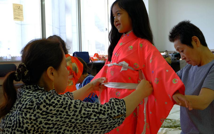 Miya Calata, 6, gives a quick smile as local Japanese volunteers make final touches to her kimono during a charity event in Yokosuka City, Japan, Sunday, June 22, 2017.