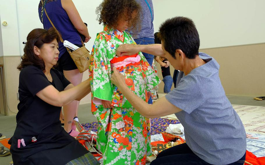 Fielding Samuels, 5, waits patiently as she is fitted into her kimono during a charity event in Yokosuka, Japan, Sunday, June 11, 2017.