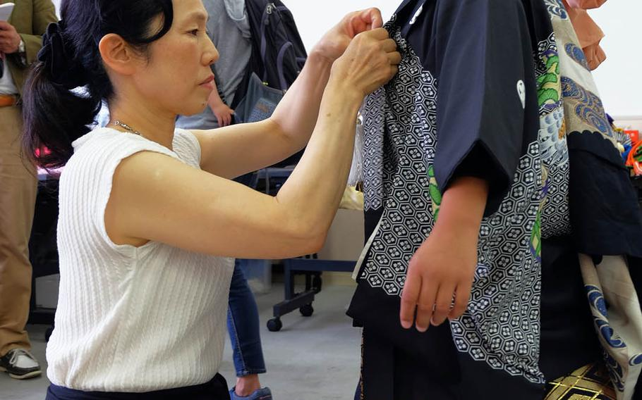 Juvenal Jimenez, age 7, inspects his kimono during a charity event for disaster victims in Yokosuka, Japan, Sunday, June 11, 2017.