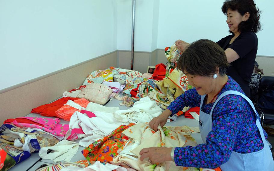 Japanese volunteers sort through a pile of kimonos, some of which are nearly 100 years old, during a charity event in Yokosuka, Japan, Sunday, June 11, 2017.