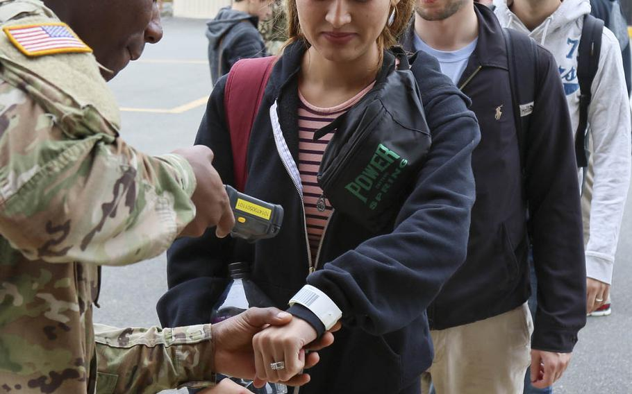 A soldier from the 8th Army's 19th Expeditionary Sustainment Command scans a family member's identification bracelet at Gimhae Air Base, South Korea, June 6, 2017, during Operation Focused Passage 17.