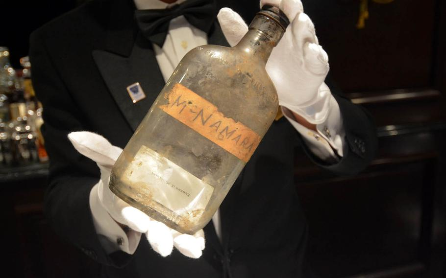 Keisuke Ohta, manager of Bar Sea Guardian II at the Hotel New Grand in Yokohama, Japan, holds the bottle found by construction workers during the hotel's recent renovation. Inside the bottle is the business card for Lt. Col. Eugene J. McNamara, a guest during the post-World War II occupation. The hotel would like to find McNamara's family.
