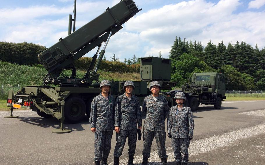 Members of Japan's 1st Air Defense Missile Group pose with a PAC3 launcher at Iruma Air Base on the outskirts of Tokyo, Friday, June 9, 2017.