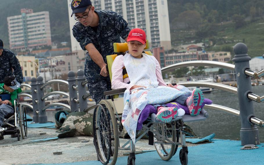 Seaman Shingo Douglass takes a walk with a resident of Aikwangwon Orphanage during a community relations project in Koje-do, South Korea, Oct. 20, 2016.