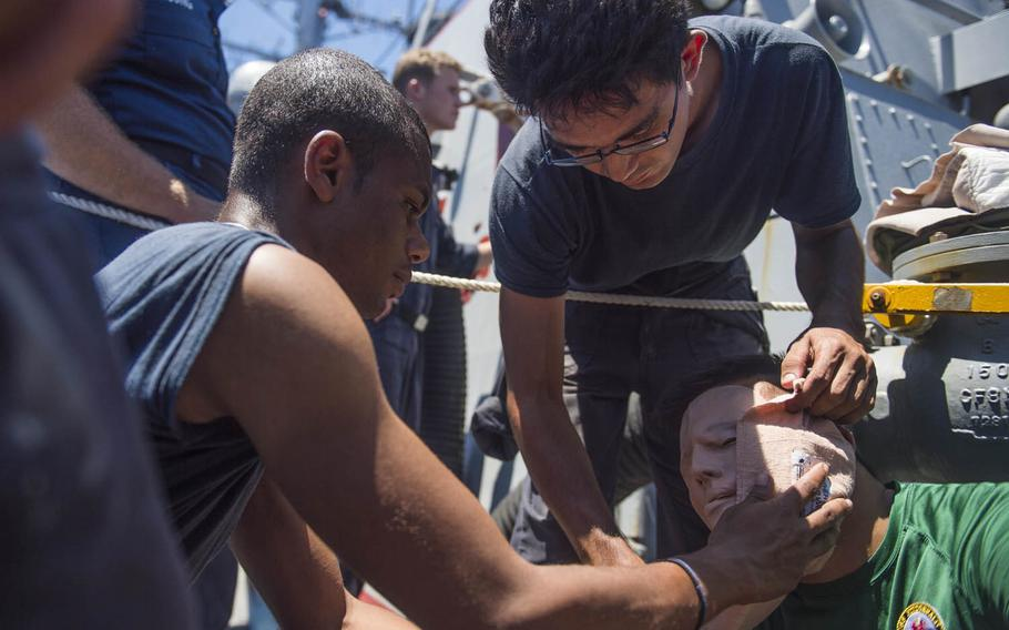 Seaman Shingo Douglass, top, and Information Systems Technician 3rd Class Alexavier Allen, left, simulate treating facial lacerations on Cryptologic Technician Seaman Nachanon Liwirun during a medical training team drill aboard the USS Fitzgerald in the Philippine Sea, Aug. 17, 2015.