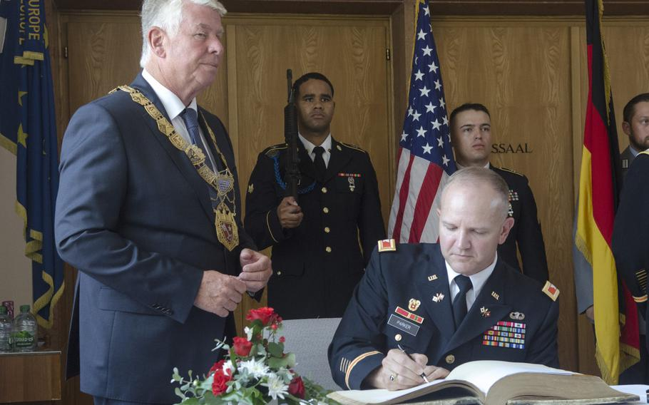 Col. Rob Parker, right, commander of the U.S. Army's 5th Signal Command, signs the golden book of Worms, Germany, in the city hall at a ceremony on Wednesday, June 21, 2017. The 5th Signal Command, soon to deactivate under Department of Defense streamlining efforts, paid a final farewell to the city.
