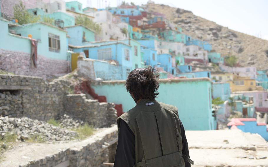 Aziz Khan, 25, looks at his neighborhood of Sher Darwaza in Kabul on June 19, 2017. Kabul Municipality recently painted the houses in the neighborhood in a bid to make the war-weary residents happier.