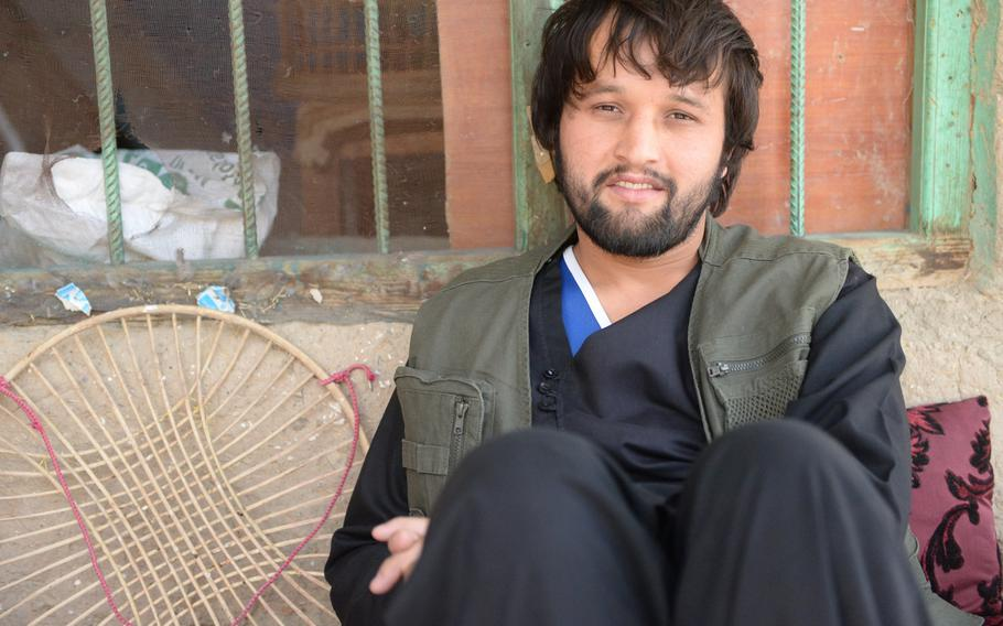 Aziz Khan, 25, sits at his home in the Sher Darwaza area of Kabul on June 19, 2017. He says the municipality's decision to paint local houses bright colors has made residents happy.