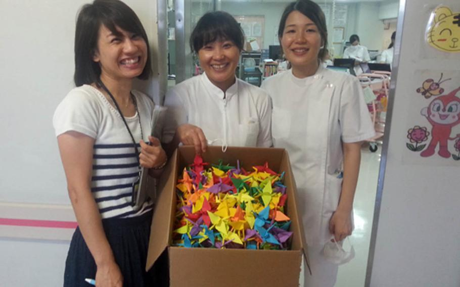 Staff members at Hobuku Hospital in Nago, Okinawa, pose with a batch of 1,000 paper cranes folded and donated by Marine Staff Sgt. Ismael Esconde.